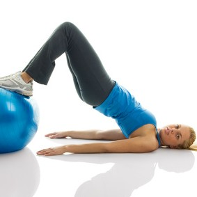 Young women training on a fitness ball. Reverse leg roll excercise; Isolated on white
