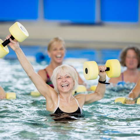 A group of seniors practicing water aerobics in an indoor pool, with one team member very excited
